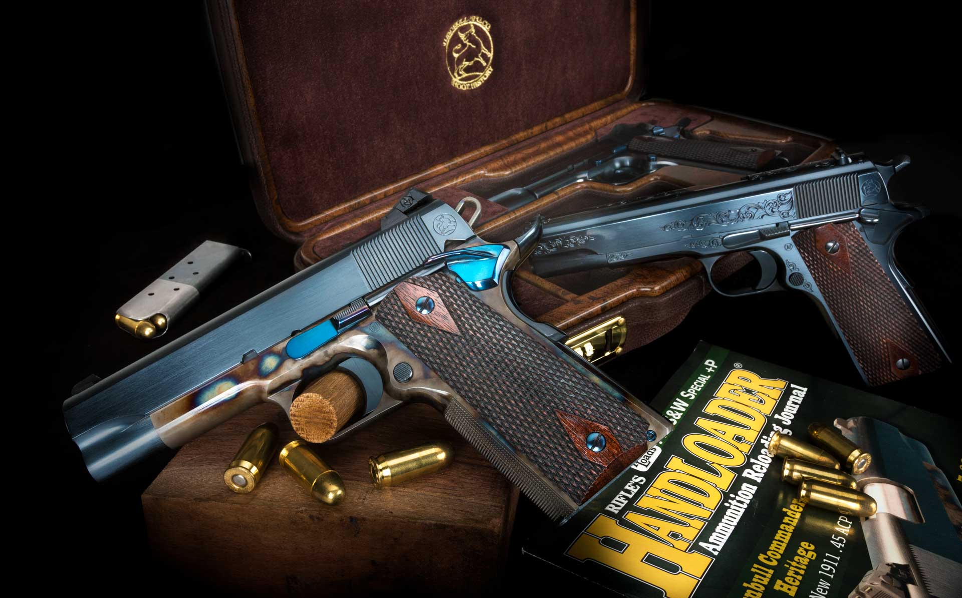 A collection of Turnbull 1911s next to an issue of Handloader Magazine