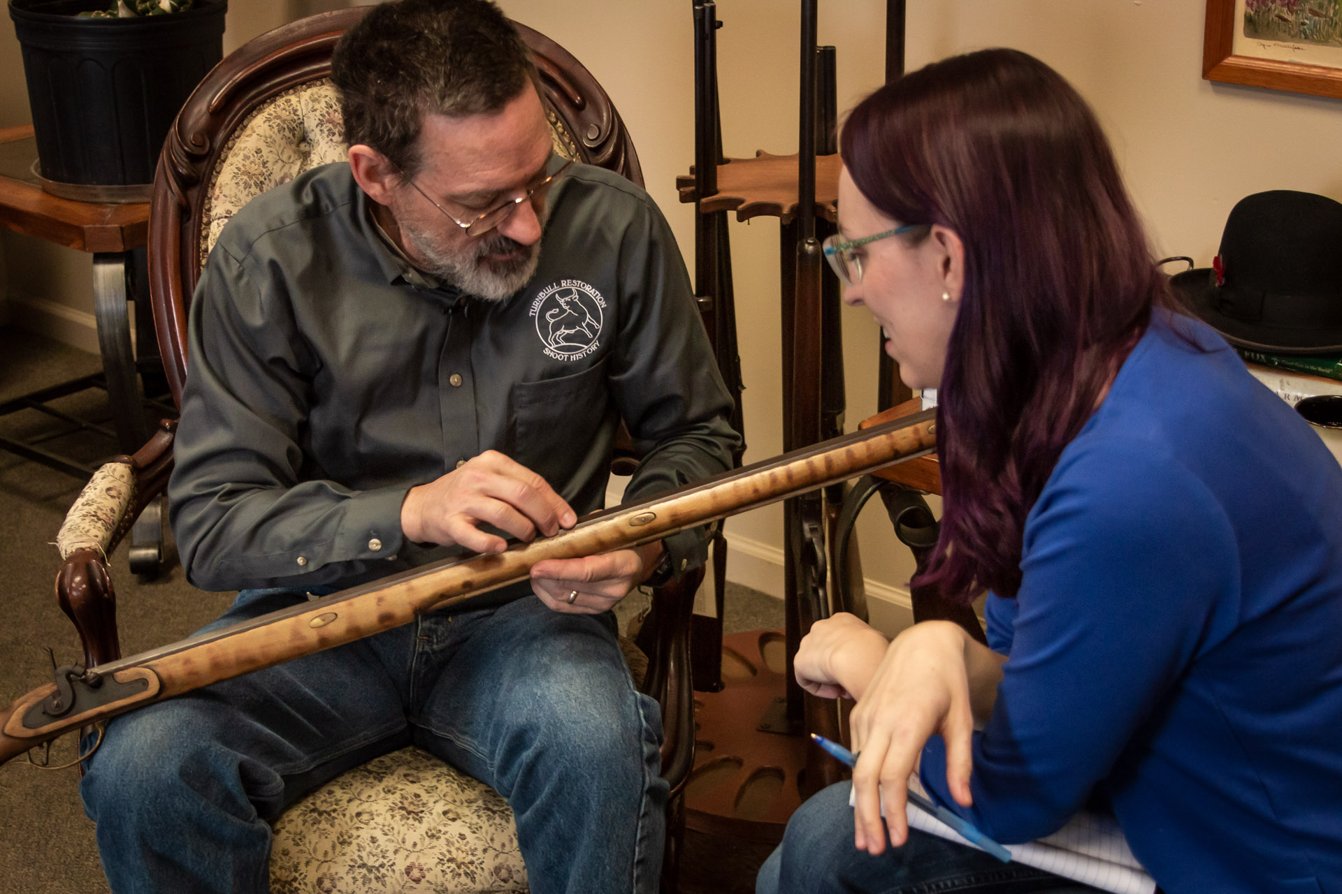 Photo of Doug Turnbull showing daughter Sara Turnbull a muzzleloader rifle that he built from a kit when he was 12 years old