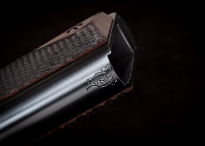 Photo of a Turnbull-made Model 1911 replica pistol, featuring hand engraving and period-correct charcoal bluing