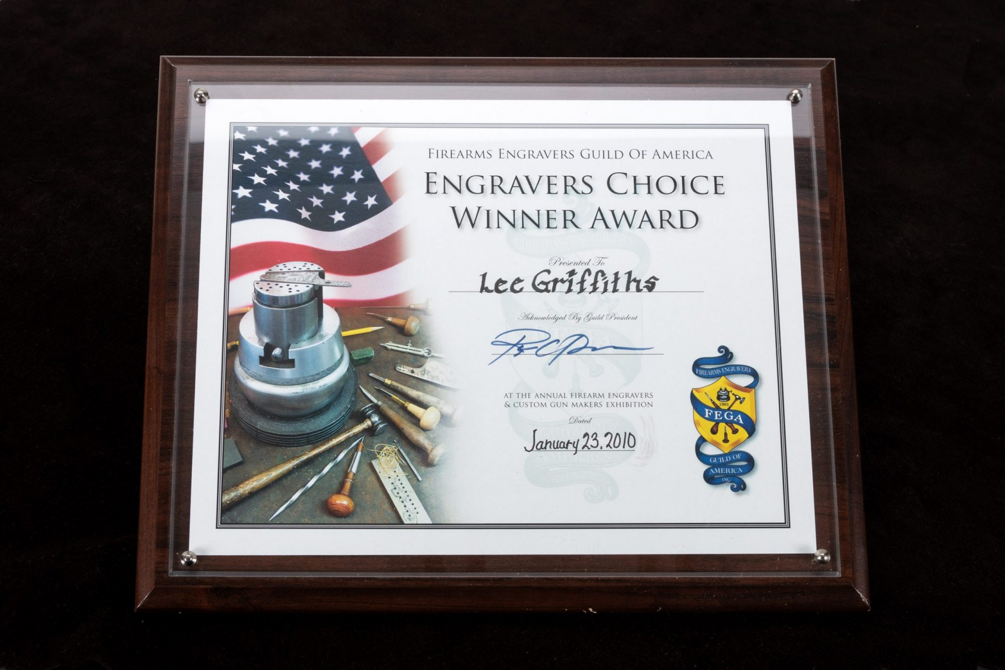 Photo of Firearms Engravers Guild of America (FEGA) award, given to FEGA Master Lee Griffiths for his work on a Navy Arms A. Uberti 1860 Henry, sold as-is by Turnbull Restoration
