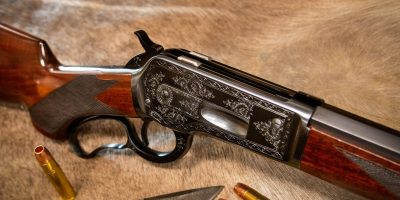 Photo of a Turnbull Model 1886, a period-correct reproduction of the famous Winchester Model 1886, featuring hand engraving and charcoal blue finish