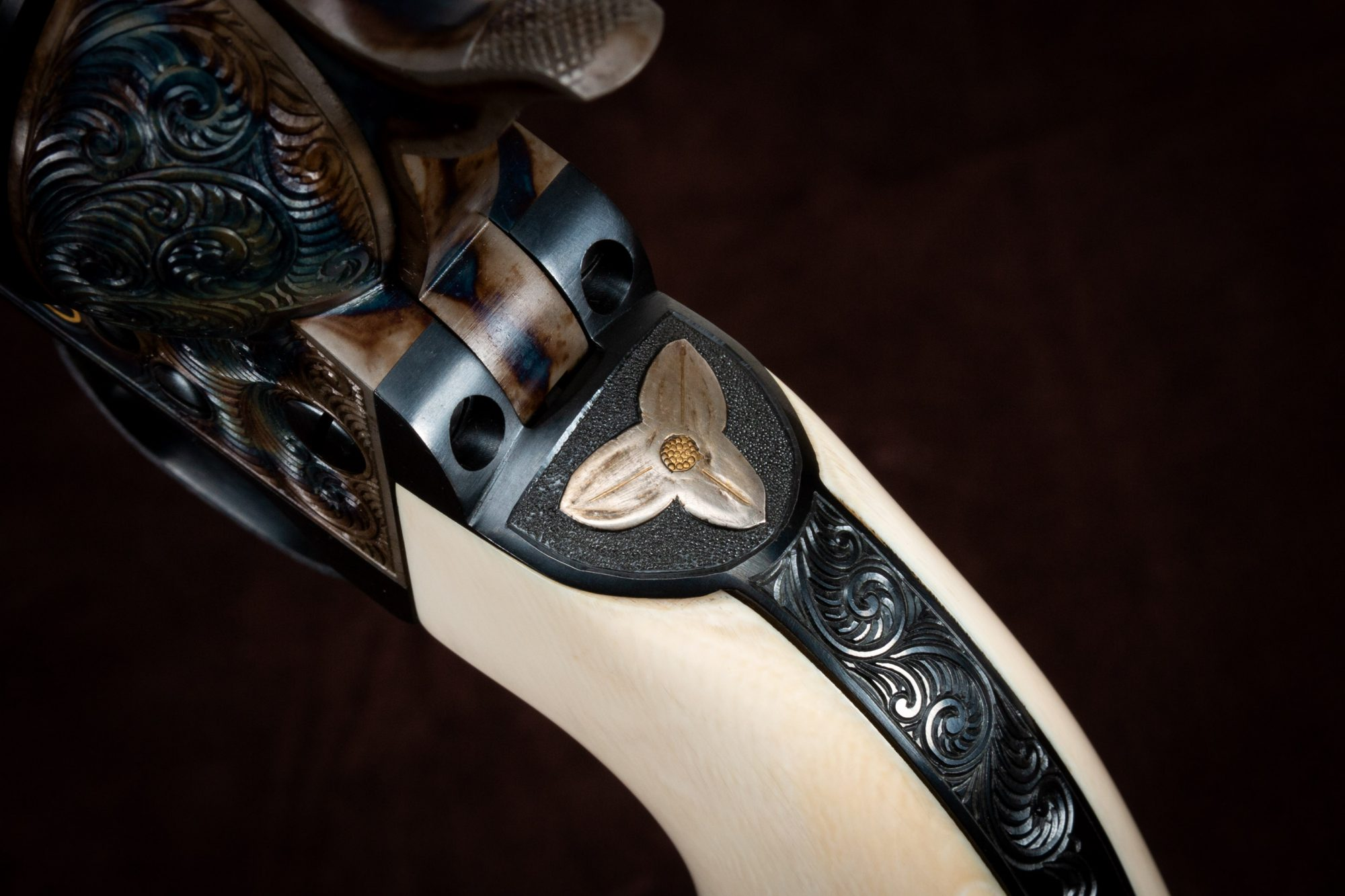 Photo of an engraved Colt SAA reproduction revolver, made by Turnbull Restoration, featuring bone charcoal color case hardening