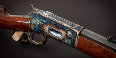 Photo of a Turnbull Model 1886 lever action rifle, featuring restoration-grade finishes like bone charcoal color case hardening, charcoal bluing and rust bluing