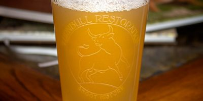 Photo of a pint glass featuring Turnbull Restoration logo in frost etching